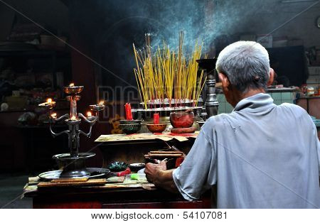 People offering incense sticks for the Gods in the Vietnamese Jade Emperor Pagoda