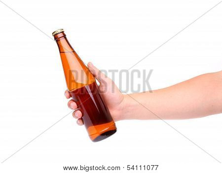 A hand holding up a yellow beer bottle