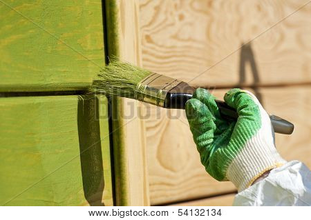 Hand with a paint brush painting wooden wall
