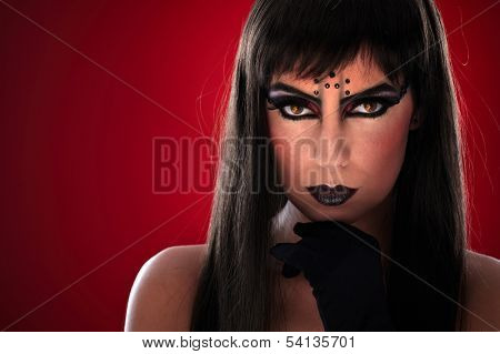 Young woman with professional black makeup and evil eyes.
