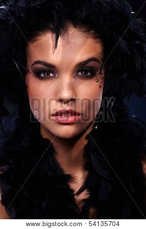Beauty in black feather boa with intense sexy look and extravagant makeup, stripes of light.
