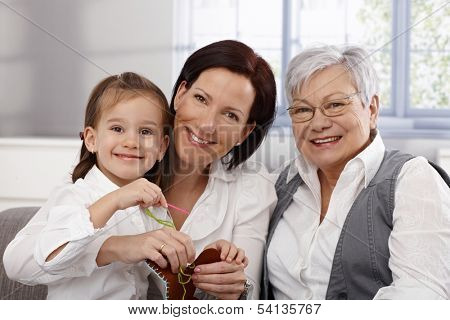 Happy generations of three women doing needlework, smiling.