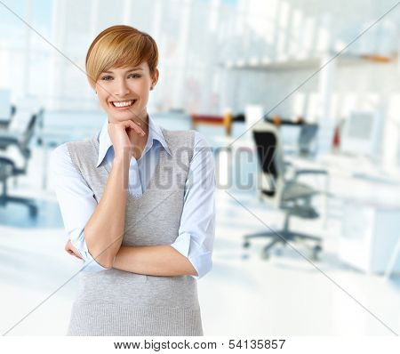 Happy caucasian woman at bright office looking at camera, smiling.
