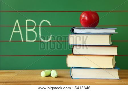 Stack Of Book And Red Apple On Desk