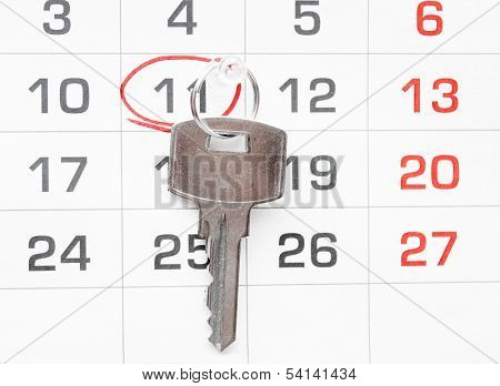 A house key on a calendar background, paying your mortgage on time