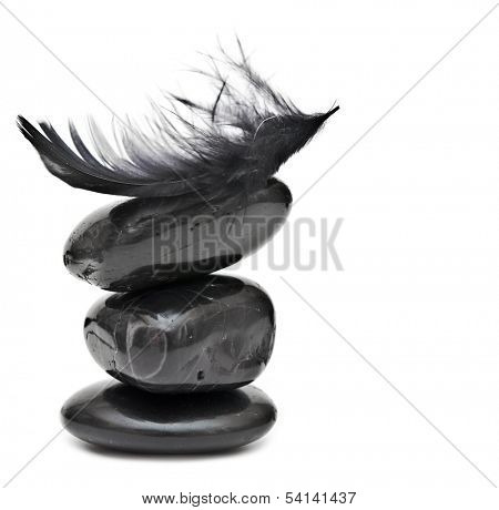 Feather balancing on stack of black stones - harmony or equilibrium concept