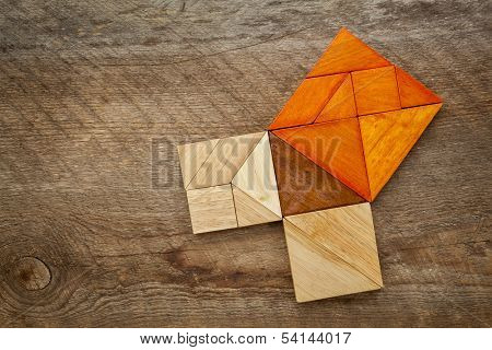 Pythagorean theorem illustrated with wooden pieces of tangram, a classic Chinese puzzle, against barn wood background