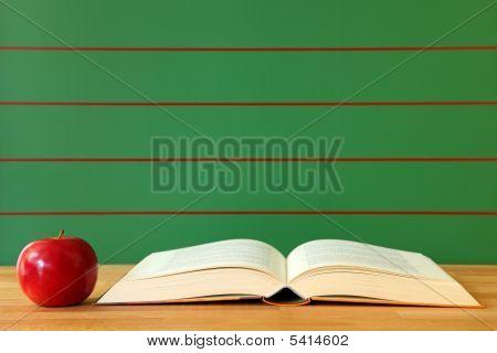 Libro abierto y una manzana roja en escritorio