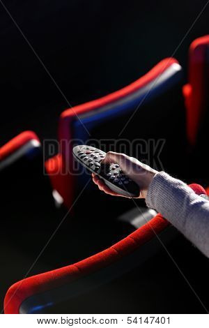 Closeup Of A Hand Holding A Remote Control Tv, In The Background You Can See The Red Chairs In A Mov