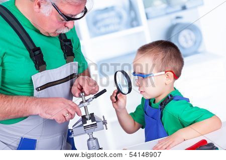 Grandfather Showing To Grandchild The Thread Cutting Die