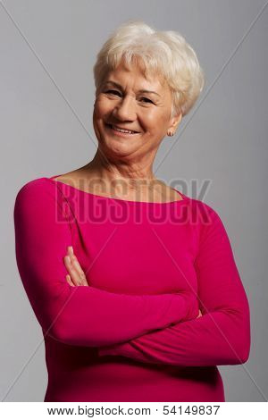 An old lady's portrait in pink casual clothes.On grey background.