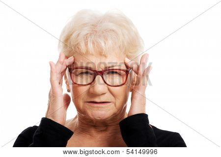 An old woman is eye glasses is having a headache. Isolated on white.