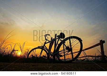 Bicycle Put Up At Wooden Fence In Sunrise