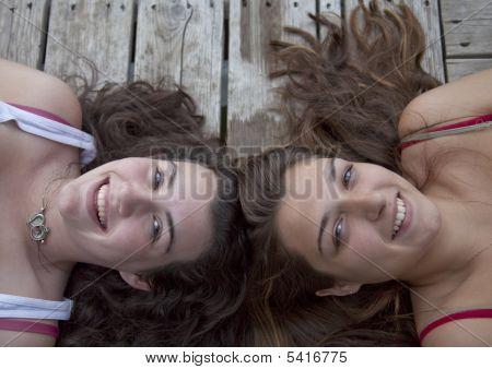 Dos adolescentes en muelle, cabeza a cabeza