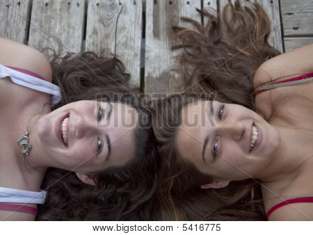 Zwei Teenager, die auf Dock, Kopf an Kopf liegen