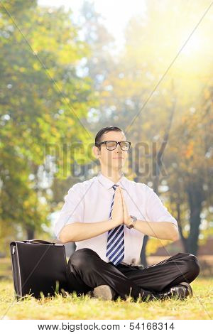 Young businessperson with eyeglasses doing yoga exercise seated on a green grass in a park