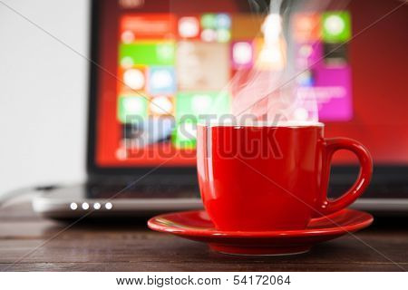 Laptop and a cup of coffee on a table