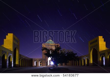 Inner yard of madrassa of Poi Kalyan oriental complex at night with star trails. Bukhara, Uzbekistan