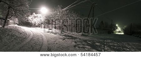 Photo of the village, snow falling on the house, night wintertime landscape