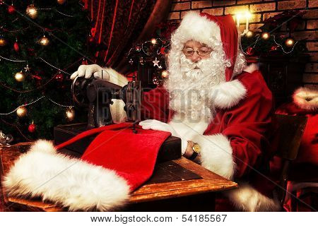 Santa Claus is sewing on a sewing machine cap for Christmas.