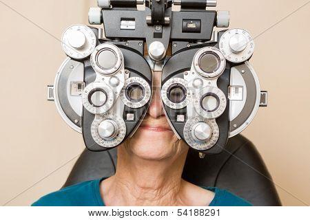 Senior woman looking through phoropter during eye exam