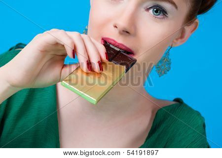 Young woman with chocolate in Studio, she have a sweet tooth and biting in a chocolate bar out of a glass