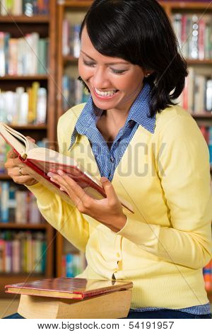 Student - a young Asian woman or girl learning in a library reading a book