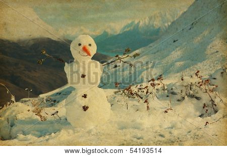 Happy snowman in mountains. Photo in retro style. added paper texture.