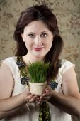 image of stewardship  - Pretty woman with small pot of bright green grass - JPG