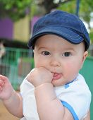 stock photo of sucking  - Baby Boy with a cap sucking finger - JPG
