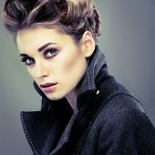 stock photo of overcoats  - Portrait of elegant young woman in a grey overcoat  on a grey background - JPG