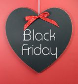 stock photo of friday  - Black Friday shopping sale concept with message on a heart shape blackboard against a red background - JPG
