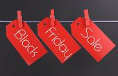 stock photo of friday  - Black Friday shopping sale concept with message written across red ticket sale tags hanging from pegs on a line - JPG