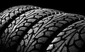 stock photo of asymmetric  - winter car tyre on a black background - JPG