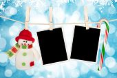 picture of candy cane border  - Blank photo frames and snowman hanging on the clothesline over blue christmas background - JPG
