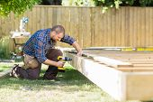 picture of carpenter  - Full length of mid adult carpenter drilling wood at construction site - JPG