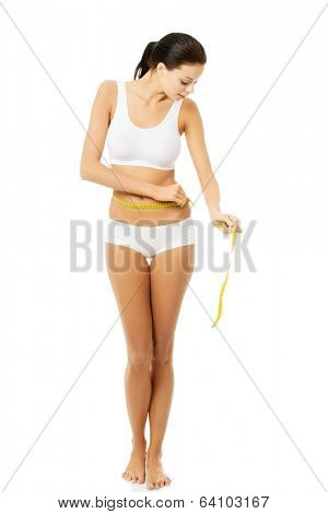 Happy young woman measuring her waist , isolated on white