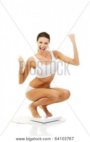 Happy woman on scales. Weight-loss concept.