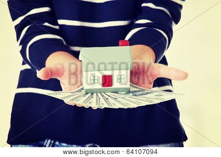 Woman holding US dollars bills and house model  - real estate loan concept