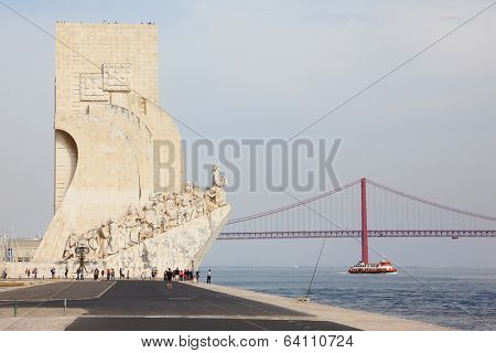 LISBON, PORTUGAL - SEPTEMBER 28, 2011: Embankment of the River Tagus - the obelisk in memory of  naval conquests of Portugal and the beautiful red bridge over the river. Lisbon, capital of Portugal