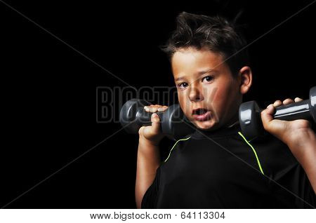 Portrait Of Handsome Kid Doing Exercise With Dumbbells