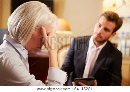 Woman Talking To Male Counsellor Using Digital Tablet