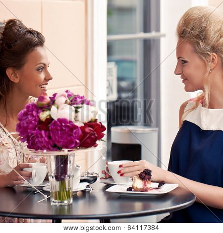 Two Beautiful Young Girls In Summer Outfit Sitting At The Table In Pavement Cafe