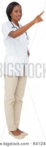 Young nurse in tunic pointing on white background