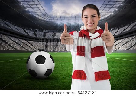 Football fan in white wearing scarf showing thumbs up against vast football stadium with fans in white