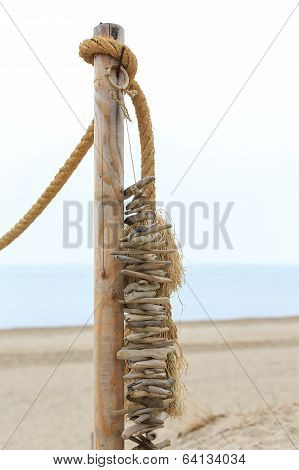 Driftwood On A String Hanging On The Beach