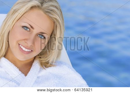 Beautiful blonde girl young woman in white spa robe with natural blue water background
