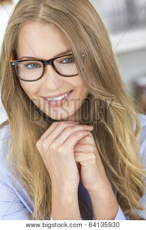 A beautiful intelligent blond girl or young woman looking happy and wearing geek glasses