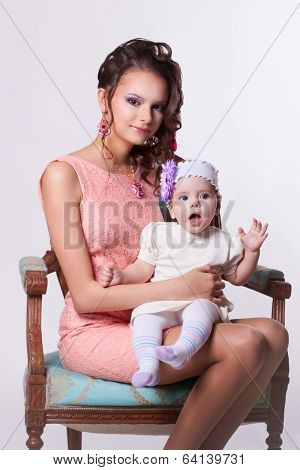 Beautiful Mother In A Pink Dress And Hairdo With Her Daughter At The Hands Of 6 Months