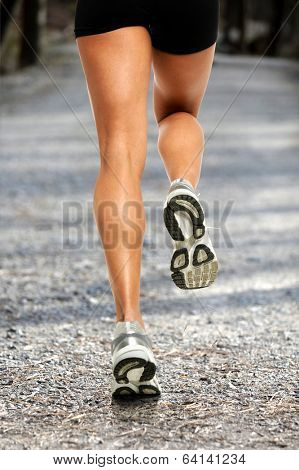 Legs of female runner on dirt gravel road